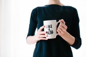 Woman holding mug with the phrase 'like a boss' printed on mug